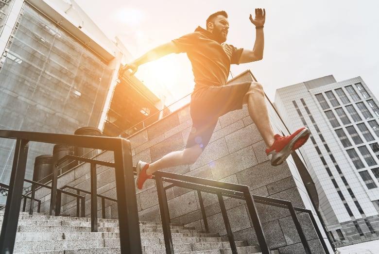 Mann der sportlich über mehrere Treppenstufen hinunterspringt